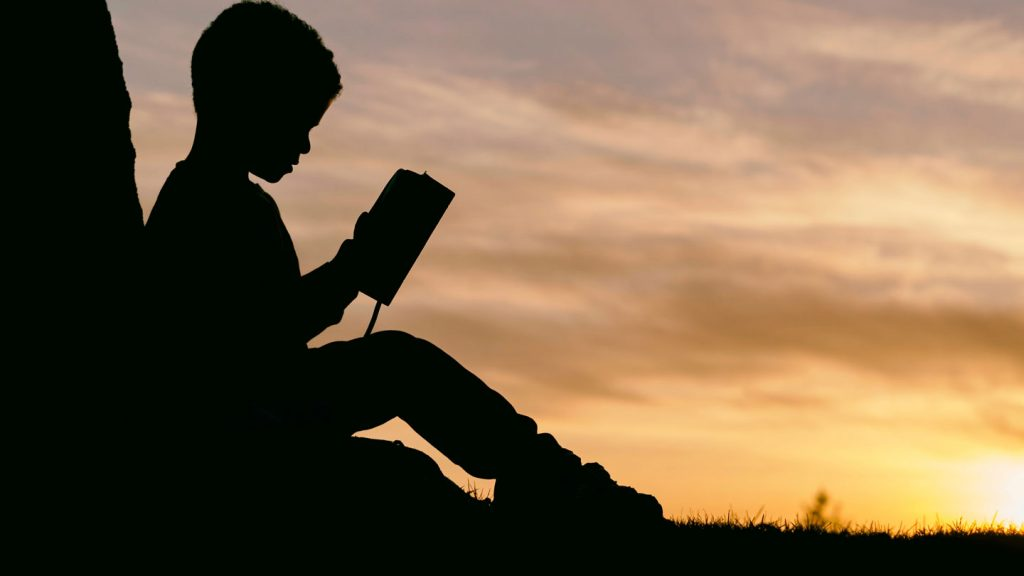 Silhouette of a boy reading at sunset.