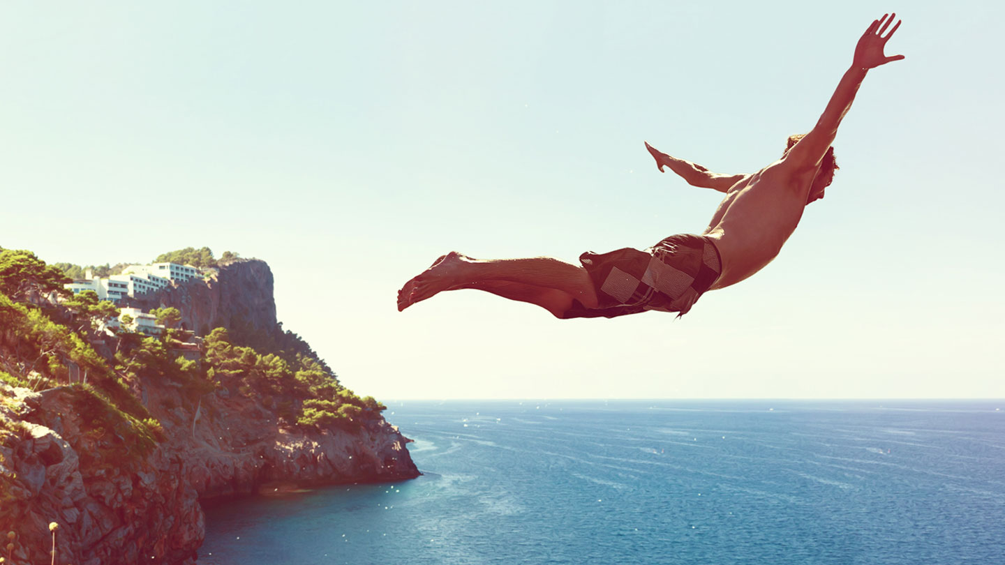 Man diving off high cliff into the sea