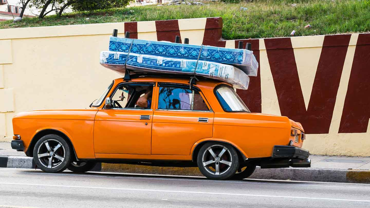 upside down mattress and bed on top of orange car