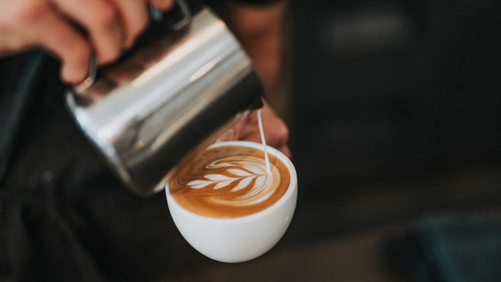 Pouring milk into an expresso