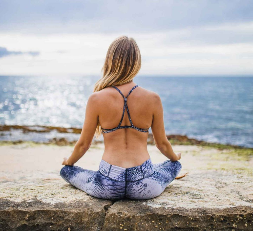 Woman meditating on cliff top facing the sea