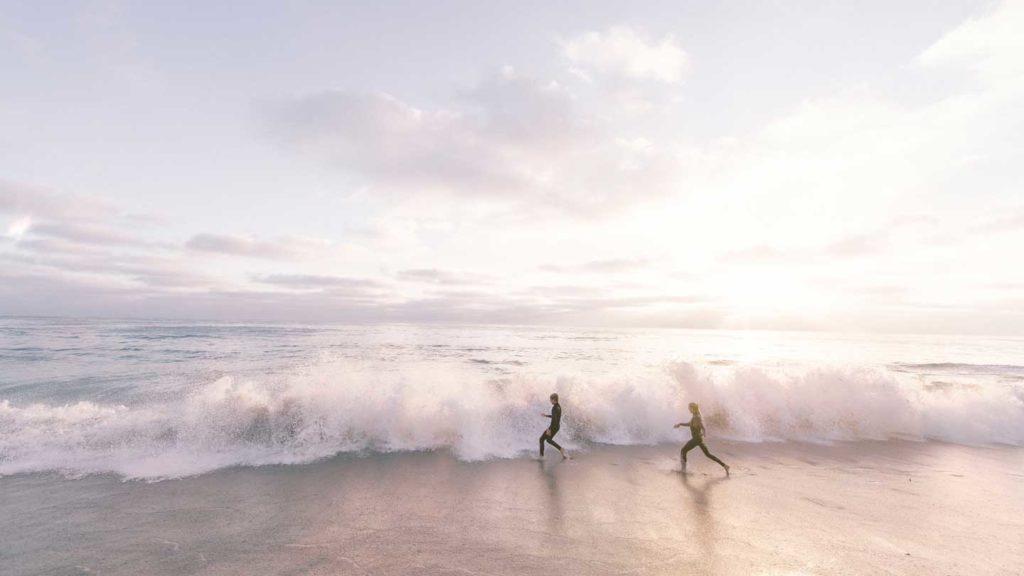 surfers running on a beach