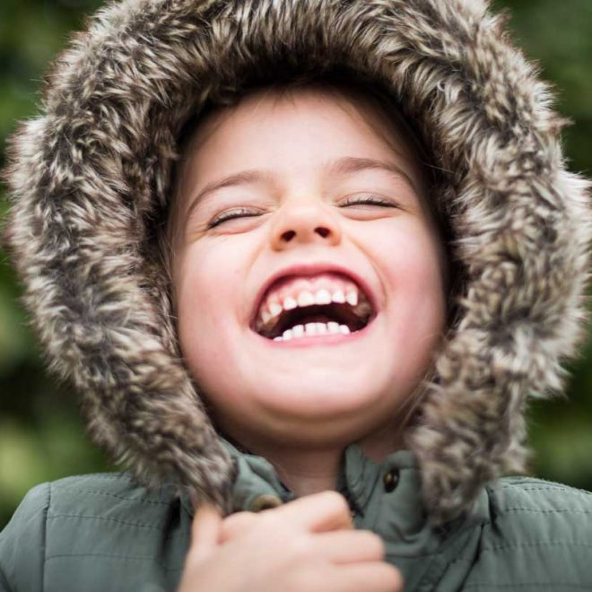 child laughing in a fur hood