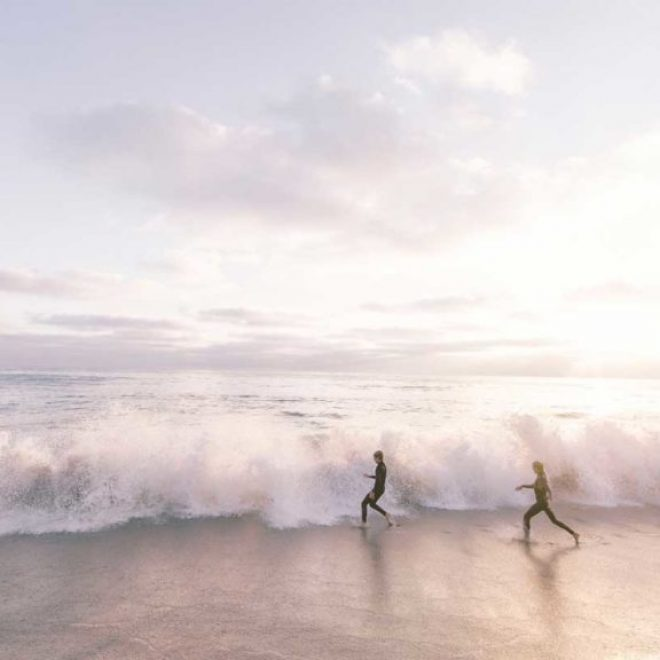 surfers running on a beach